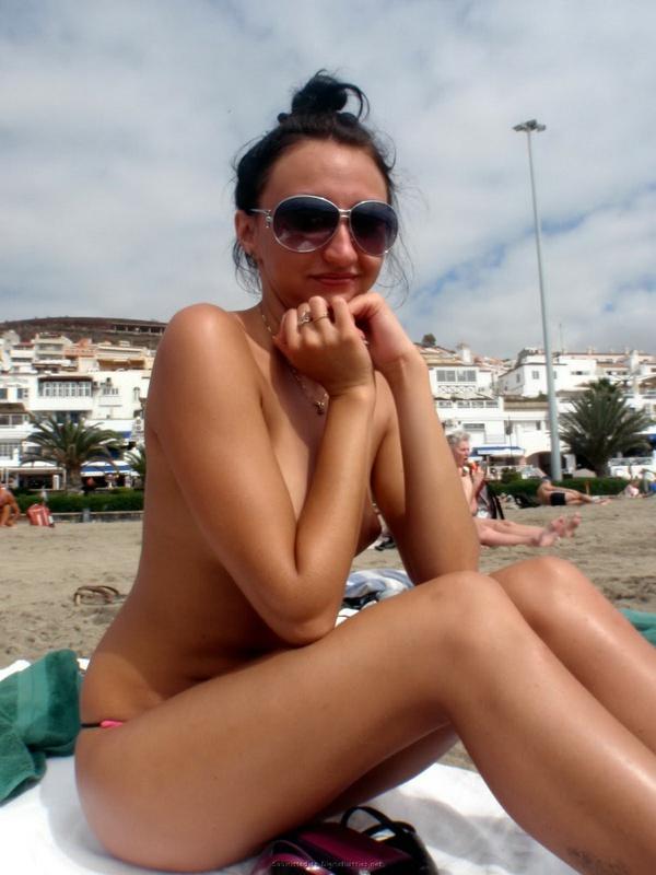 Развратная девушка загорает на пляже топлесс - порно фото