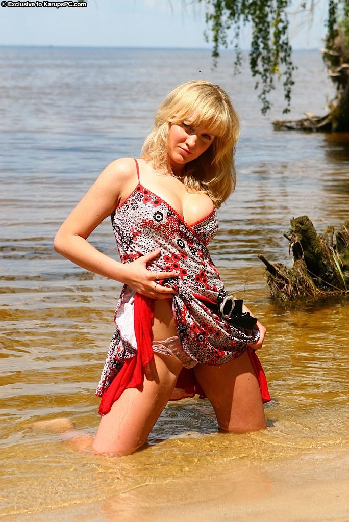Блондинка в платье зашла в воду, показала стриптиз и присела на бревно - порно фото